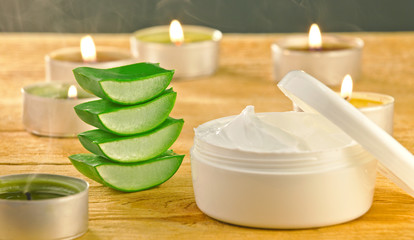 Fresh aloe vera slices and cream container on wooden.