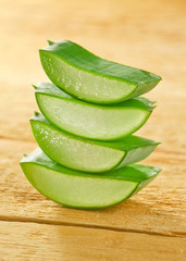 Fresh aloe vera slices on wooden with some candles.