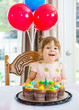 Girl Sitting In Front Of Cake At Home