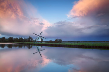beautiful sunset over Dutch windmill by river