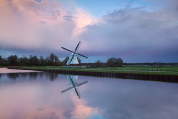 Pink rainy sunset over windmill by river
