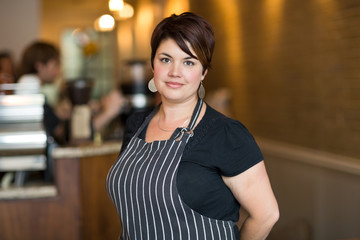 Confident Female Owner Smiling At Cafeteria