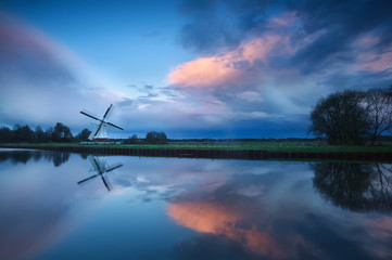 dramatic stormy sunset over windmill by river