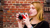 Hipster girl taking photos with vintage camera