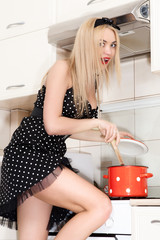 Beautiful young housewife in the kitchen. A girl holding a pot