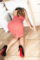 The woman put her head in the washing machine.