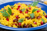 couscous salad with curry, dried cranberries and herbs, close-up