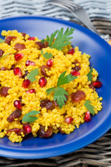 couscous salad with curry, dried cranberries and herbs, vertical