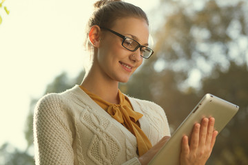 Closeup of young smart woman with tablet outdoors