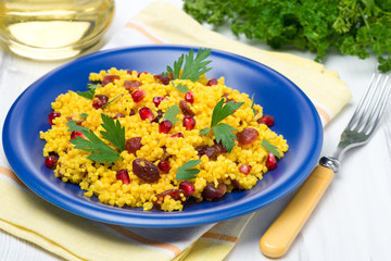 couscous with curry, dried cranberries and herbs on the plate
