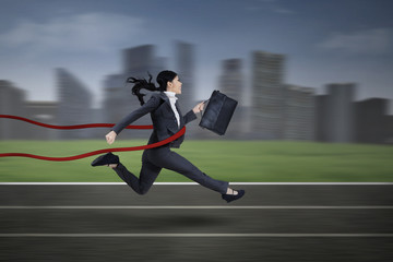 Asian businesswoman winning a race