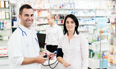 Pharmacist check woman blood pressure