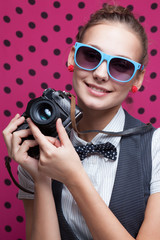 Portrait of trendy smiling girl with retro camera