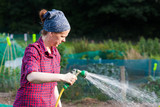 Young woman using a garden hose nozzle