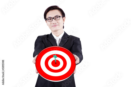 Smiling businessman holding a dartboard