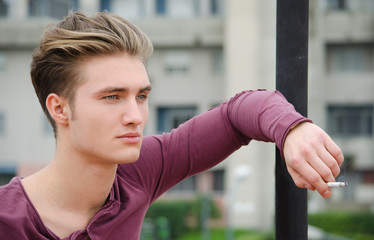 Handsome blond young man smoking cigarette
