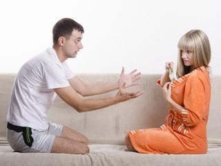 Жена прячет от мужа пачку денег в халат, сидя на диване