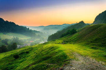 hillside near the village in morning mist © Pellinni
