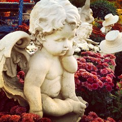 Little girl sculptures in ornamental garden decoration