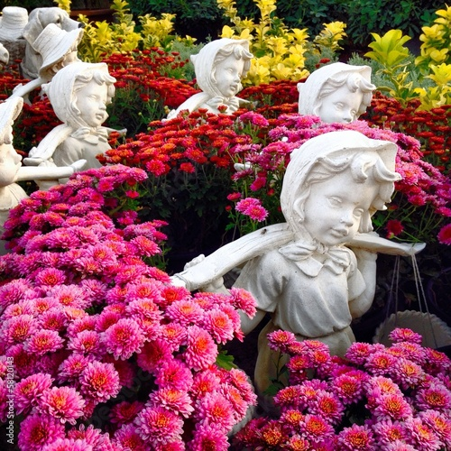 Little girl sculptures in ornamental garden decoration