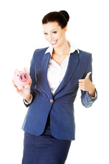 Attractive young business woman holding piggy-bank and showing O