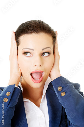 Attractive business woman covers her ears.
