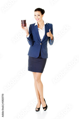 Attractive young business woman holding a cup and showing OK.