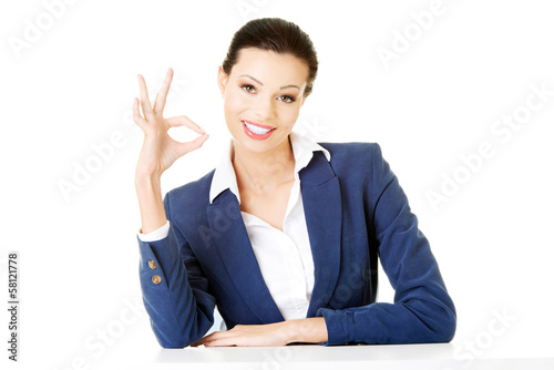 Attractive business woman showing OK and sitting.