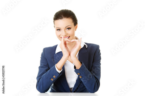 Attractive business woman showing heart sign.