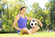 Young athlete female sitting on a grass and holding a football