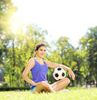 Young athlete female sitting on a grass and holding soccer ball