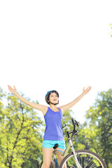 Happy female biker posing with raised hands on a bike in a park