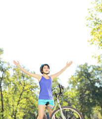 Happy female biker posing with raised hands on a bike outdoors