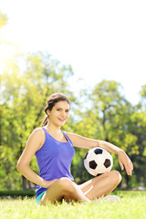 Young athlete female sitting on a green grass and holding ball