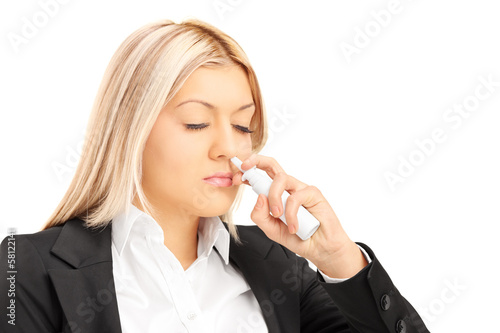 Young blond female spraying drops in her nose