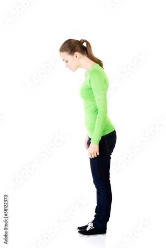 Attractive young woman standing and looking down. Side view.