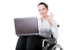 Business woman sitting on wheelchair, showing OK.