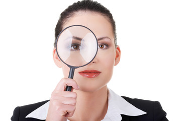 Business woman looking through magnifying glass.