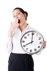 Business woman holding a clock and yeaning.