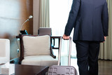 Manager in suit moving into hotel room with his suitcase