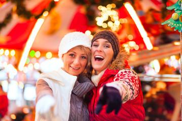 Freundinnen auf Weihnachtsmarkt in Adventszeit