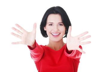 Attractive woman in red tshirt with open hands.