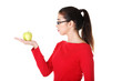 Attractive woman in eyeglasses with apple on hand.