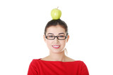 Portrait of attractive young woman with apple on head.