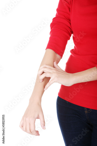 Attractive woman scratching herself. Hand closeup.