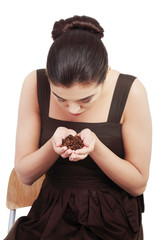 Beautiful woman sitting and holdig coffee beans in hands.