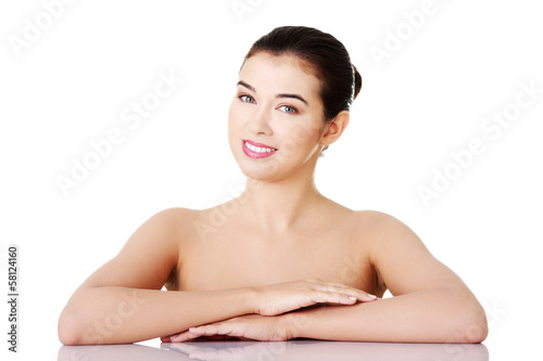 Naked woman sitting by table.