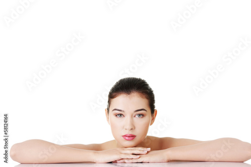 Naked woman lying on hands on a table.