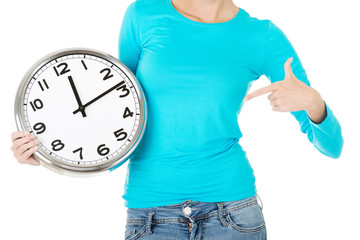 Attractive woman with a clock. Close up. Bodypart.