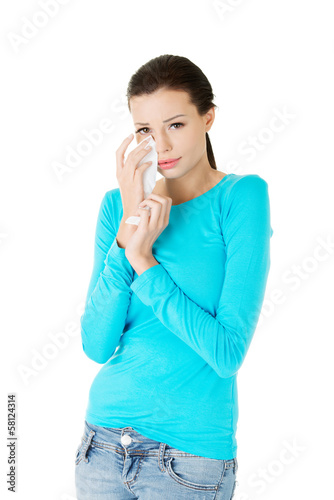 Attractive woman crying, holding a tissue.